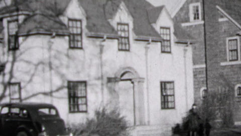 1937: Wealthy suburban white brick house car parked in driveway Footage
