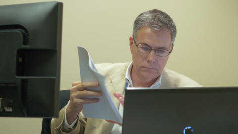 businessman looking at paperwork at his desk 4k Footage