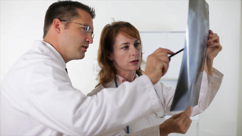 doctors looking over xray Footage
