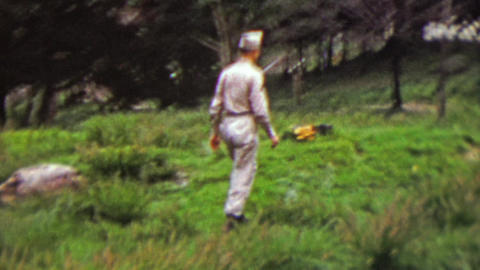 1951: Military soldier hiking in rural green grassy park Footage