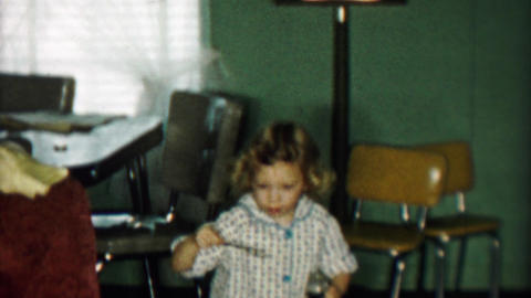1957: Young girl blowing soap bubbles indoor kitchen table Footage