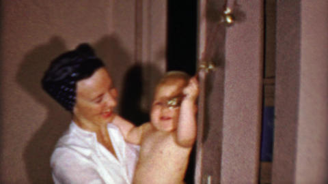 1953: Baby boy ringing bells in Rosie the Riveters style woman arms Footage