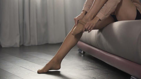 Elegant woman going on date, putting nylon tights on her beautiful legs Live Action