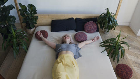 Top view, beautiful blonde fun lies in the big bed and breaks her arms. Smiling Live Action