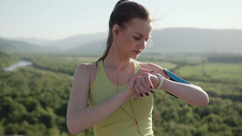 A young sports girl in sports wear who runs in the fresh air in the mountains at Footage
