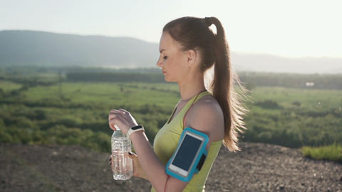 Fitness young woman drinking water from sport bottle. Cold drink after running Footage