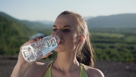 Attractive sport girl drinking cold water after running in the mountain in the Footage