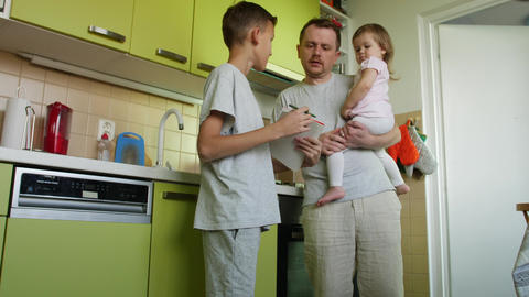 Cooking father holding girl in arms helps son with homework in kitchen ビデオ