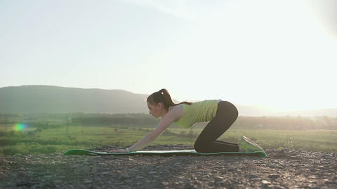 Cute fit young woman doing warming up stretching on a nature. Sport fitness Live Action