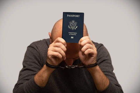 Man in handcuffs with American passport Fotografía