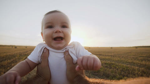 Young dad holds in the hands of first person in the field. First - person view Footage