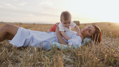 Young woman with her adorable 6 month boy playing outdoors in the field. A young Live Action