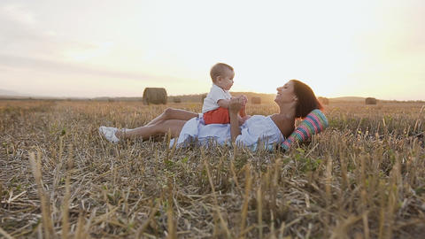 Young woman with her adorable 6 month boy playing outdoors in the field. A young Footage