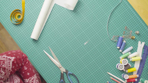 Middle-age woman hands with scissors cutting paper template. Handmade cloth Footage