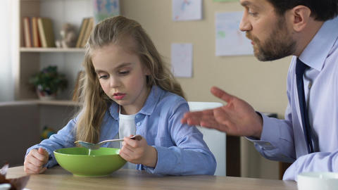 Strict father shouting at daughter, forcing to eat, demanding man scolding child Live Action
