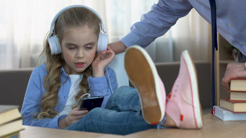 Strict father shouting at daughter listening to music in headphones in room Live Action