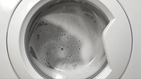 Clothes is washing in the washer with a lot of foam, in the laundry, washday Footage