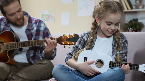 Father guitar and daughter ukulele playing song, creative leisure, rehearsal Footage