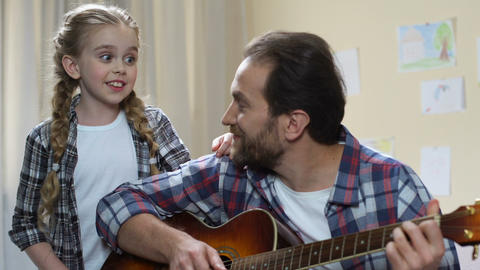Talented daughter singing while father playing guitar, musical hobby, having fun Footage