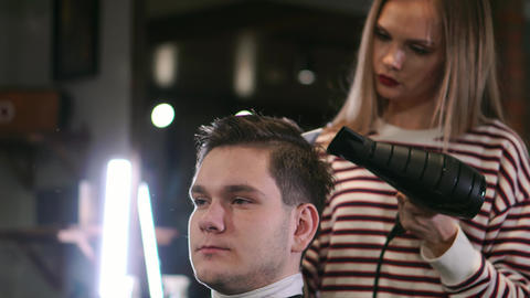 Male hairstyle in salon. Man hair drying in barber shop. Barber styling hair Footage
