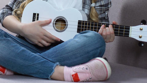 Girl learning to play ukulele, musical hobby, children creativity, free time Live Action