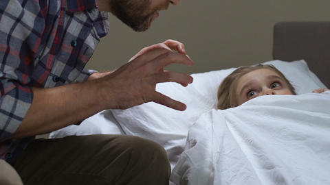 Father telling scary fairytale daughter, spending time together, family fun Footage