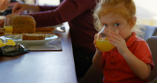 Cute little boy drinking orange juice at dining table 4k Live Action