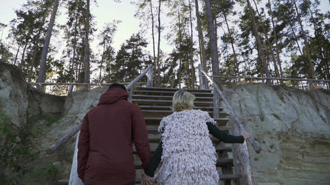 Young guy and the girl hold the hand and climb the wooden stairs. Young couple Footage