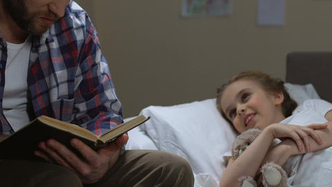Girl in bed listening to father reading book before sleep, happy childhood Footage