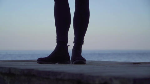 Female legs standing on a wooden platform outdoors. Legs of a woman in tight Live Action