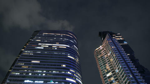 Modern design skyscrapers illuminated at night time in city center, close up GIF
