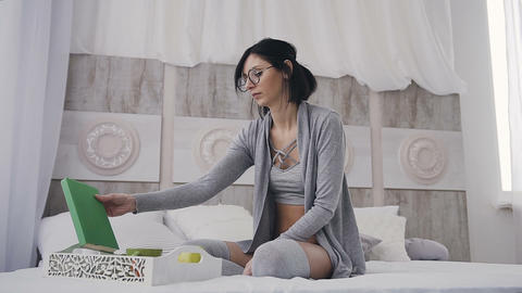 Beautiful girl in glasses opens a book for reading. Woman reading book or diary Live Action