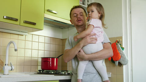 Father with daughter in hands lauds son for writing in kitchen ビデオ