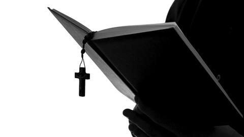Priest silhouette reading Bible, celebrating Mass, religious sect, close up Footage