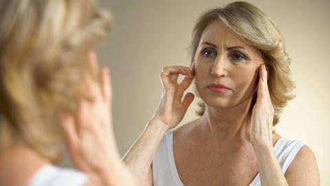 Unhappy aged woman looking in mirror at home, touching her face, aging process Footage