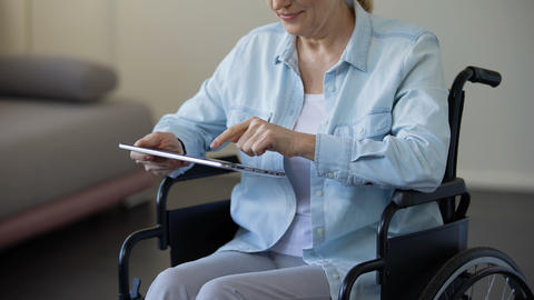 Grandmother sitting in wheelchair and scrolling family photos on tablet, gadget Live Action