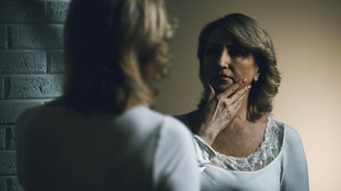 Sad senior female looking in mirror with disgust, aging problem, insecurities Footage