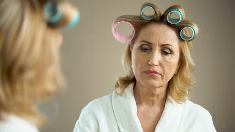 Aged sad woman with hair curlers and make-up looking at mirror reflection Live Action