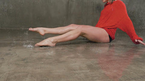 Wet woman dancer in red sweater and black short performs modern dance on the Live Action