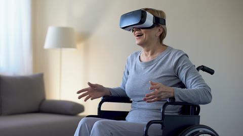 Impressed grandmother in wheelchair wearing goggles, playing VR game, device Footage