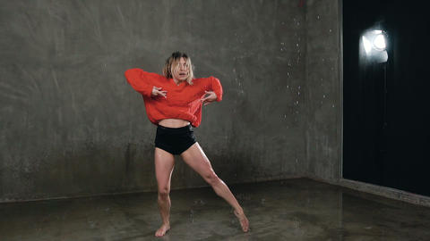 Young professional female dancer is performing acrobatic dance in studio under Live Action