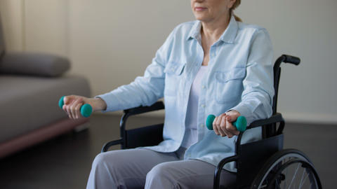 Elderly female in wheelchair lifting dumbbells at rehabilitation center, trauma Live Action