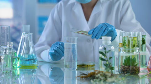 Female chemist pouring cosmetic oil in test liquid, body care production, aroma Footage