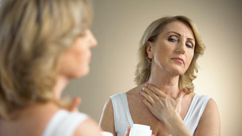 Old woman applying nourishing cream on neck and decollete zone, anti-age care Live Action