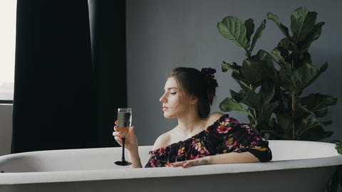 Glamour young woman drinking champagne, relaxing in bathtub after a hard working Live Action