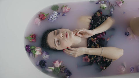 Beautiful fashion model girl in milk bath with fragrant flowers of buds Live Action