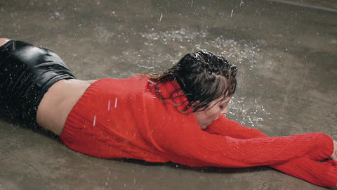Wet young woman in red sweater and black shorts is dancing on the floor under Live Action
