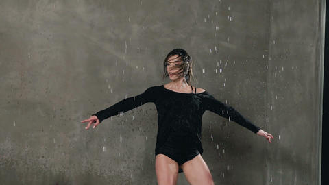 Wet dancer dancing under the drops of water in the studio before studio light Live Action