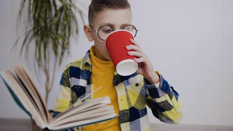 Six-seven year old boy with adult glasses read the book Caucasian boy sits on Footage