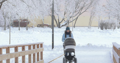 Mom with a stroller in the winter park Footage